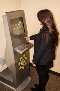 A woman uses the Ventura County Probation kiosk