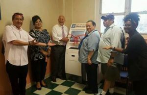 NYCHA Press Release Photo: Staff Standing with NYCHA OneStop Housing Authority Kiosks