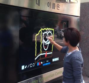 Girl draws on Austin Convention Center Interactive Kiosk
